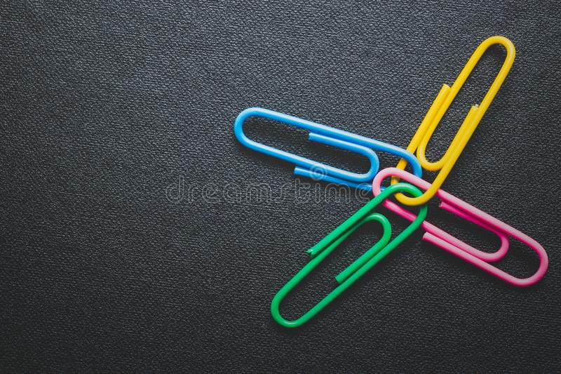 Paper clips on black background. Teamwork and success concept stock images