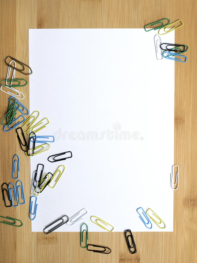 Paper clips and blank paper. On wooden background stock photo
