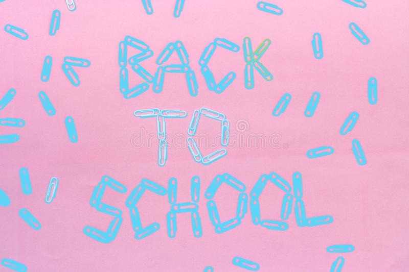 Paper clips lined with the inscription - back to school. the photo is toned in two colors - pink and blue. The view from the top stock photography