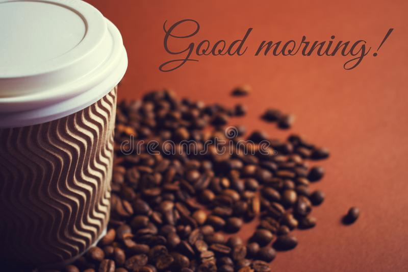 Paper coffee cup and beans on brown background royalty free stock images