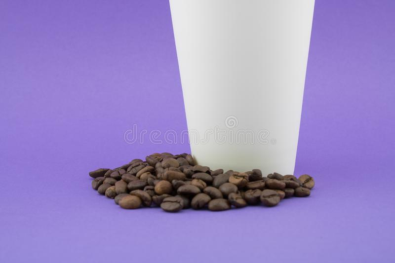Paper coffee cup on coffee beans. royalty free stock image