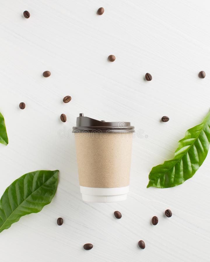 Paper coffee cup with coffee beans and leaf on white wooden back royalty free stock photography