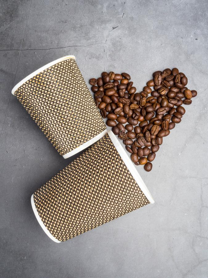 Paper coffee to go cups and heart made from coffee beans, mock up paper cups, copy space. Top view paper coffee to go cups and heart made from coffee beans, mock royalty free stock photo