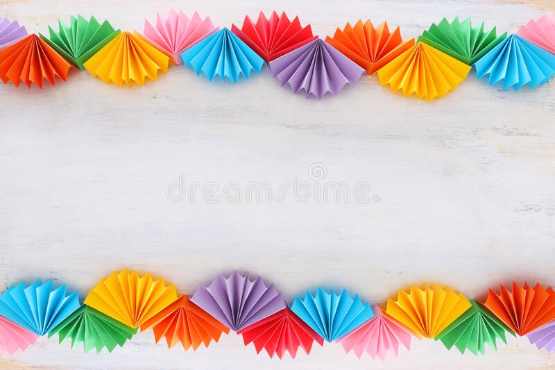 Paper colorful chain garland over white wooden background. Traditional jewish sukkot holiday decoration royalty free stock photos