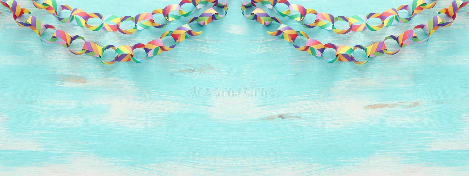 Paper colorful chain garland over white wooden background. Traditional jewish sukkot holiday decoration royalty free stock photo