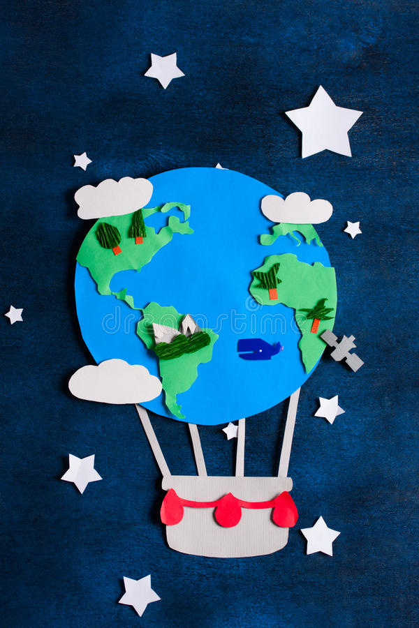 Paper craft earth globe handmade on blue wooden background. stock photos