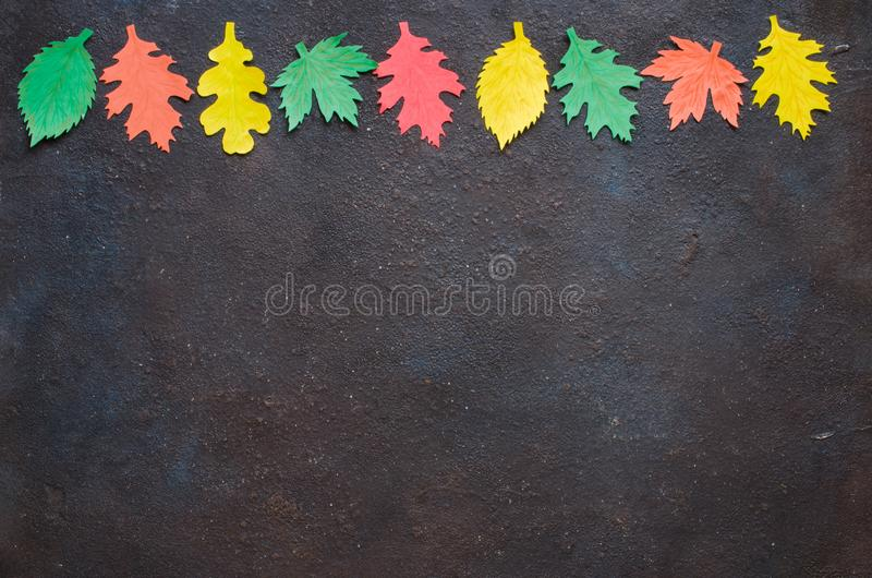 Paper craft, red and yellow Autumn leaves.Top view on flat lay on dark concrete background royalty free stock photos
