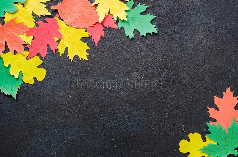 Paper craft, red and yellow Autumn leaves.Top view on flat lay on dark concrete background royalty free stock image