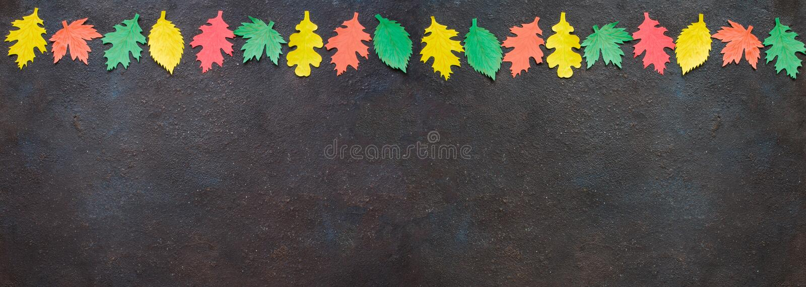 Paper craft, red and yellow Autumn leaves.Top view on flat lay on dark concrete background stock images