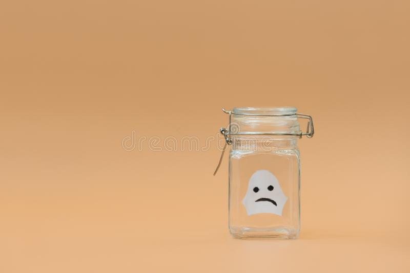 Paper craft. White ghost in glass jar on orange background. Halloween celebration concept. Copy space stock photo