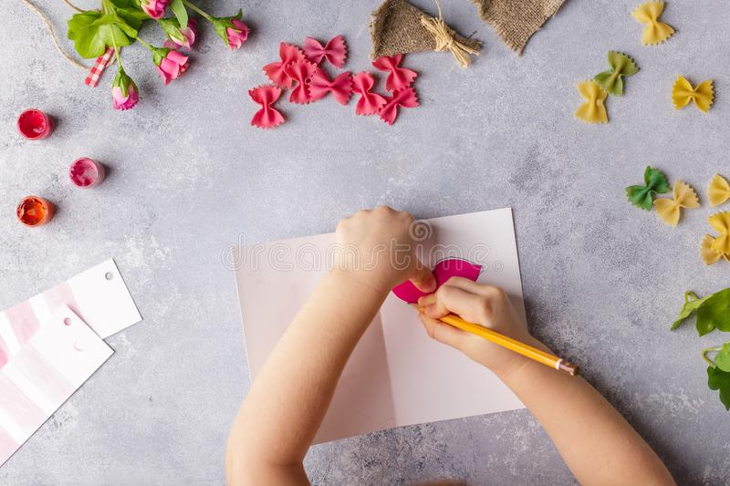 Paper crafts for mother day, 8 march or birthday. Small child doing a bouquet of flowers out of colored paper and colored pasta. stock photos