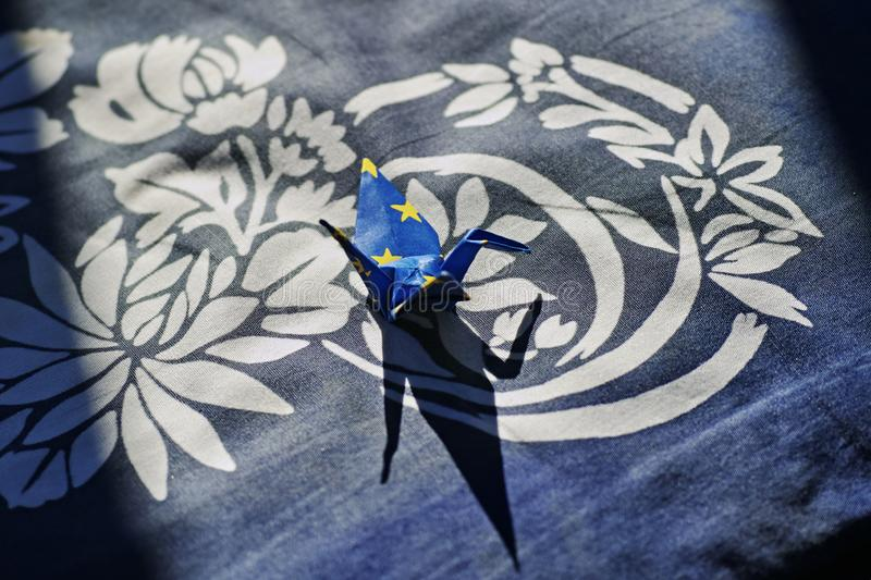 Paper Crane on the handwoven cloth. Photo taken in Takayama Japan. The hand made paper crane on the blue handwoven cloth. The sunshine gives it a beautiful royalty free stock photo
