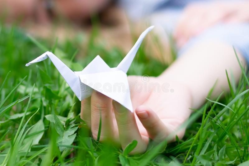 Paper crane on young girl`s hand lying on grass with closed eyes, concept of loosing love, hopfullness or life drama royalty free stock image