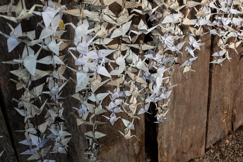 Paper cranes hanging from strings against old barn wood, vintage ephemera, folded origami, selective focus stock photography