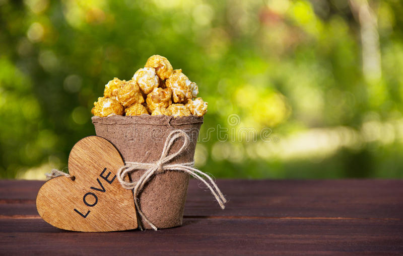 A paper cup with caramelized popcorn and a wooden heart. Golden popcorn on green natural background.Copy space royalty free stock photo