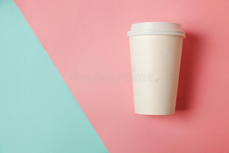Paper cup of coffee on blue and pink background royalty free stock images