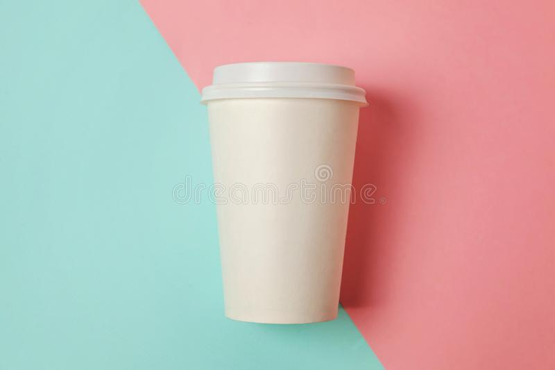 Paper cup of coffee on blue and pink background royalty free stock photo