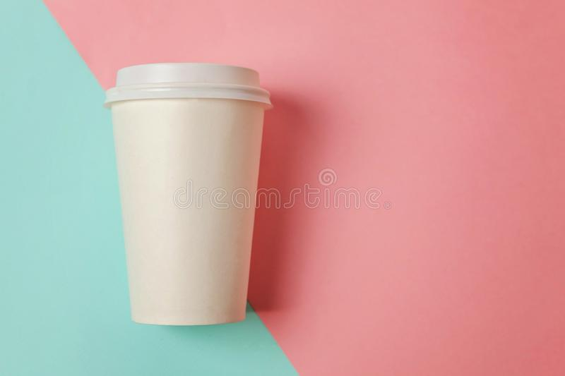 Paper cup of coffee on blue and pink background stock photos