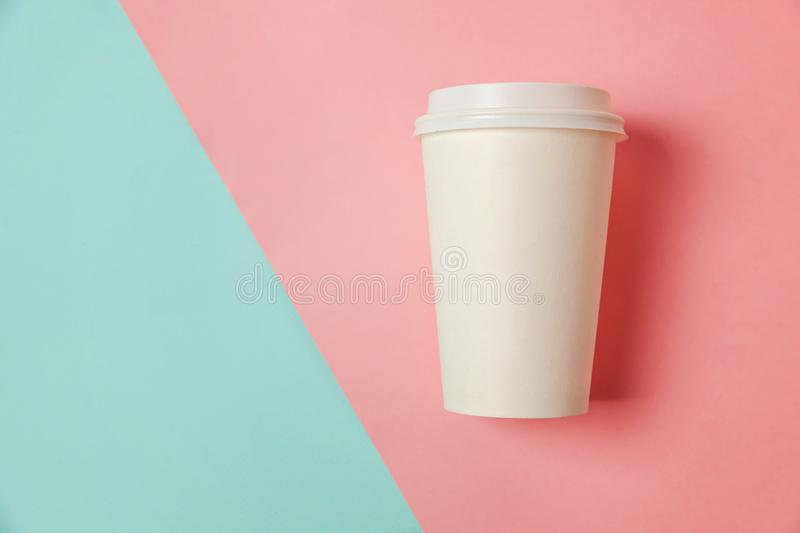 Paper cup of coffee on blue and pink background stock images