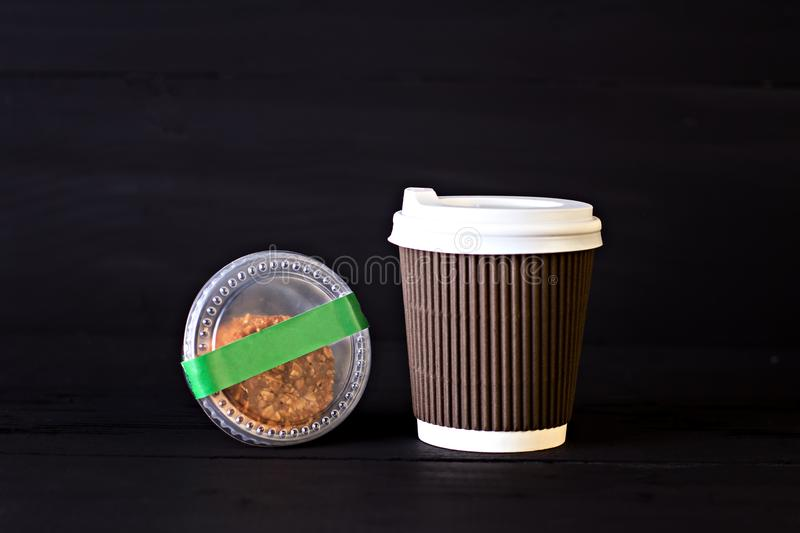 A paper cup with coffee and a box with biscuits. On a black background stock photography