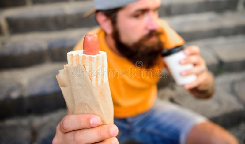 Paper cup coffee and hot dog street food traditional snack. Man hipster have quick lunch sit stairs background. He likes stock photo
