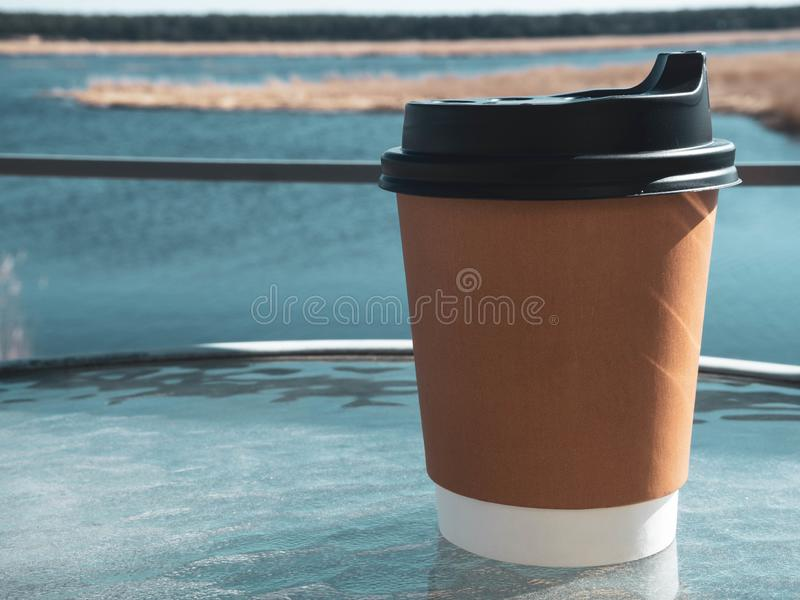 Paper cup of coffee on natural morning background. Film effect. Paper cup of coffee from paper on glass table morning background. Film effect royalty free stock image