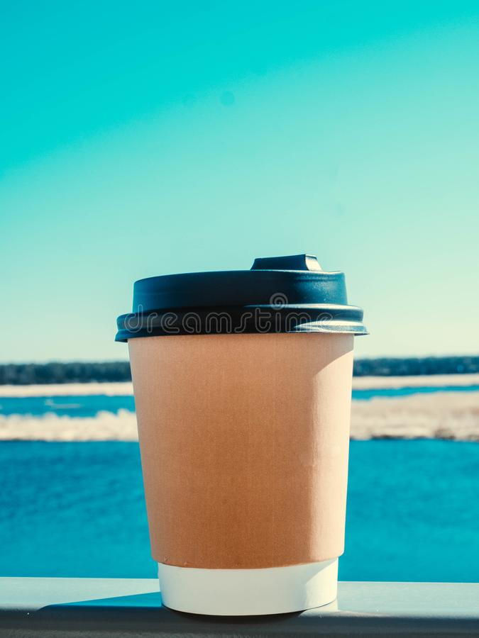 Paper cup of coffee on natural morning background. Film effect. Paper cup of coffee from paper on teracce morning background. Film effect stock photos