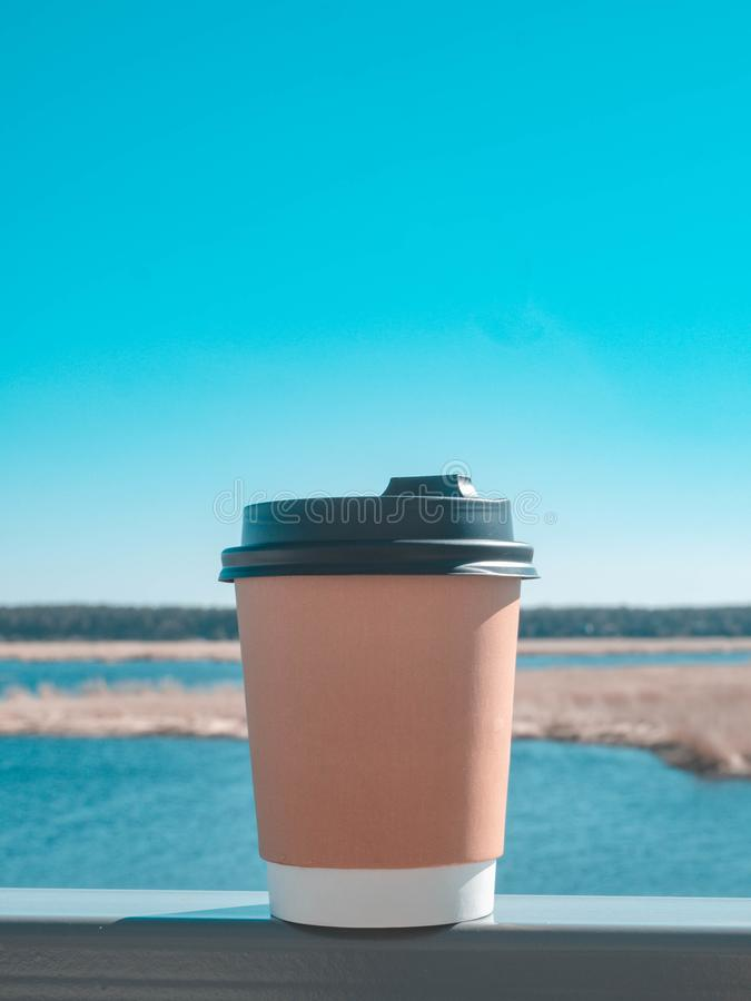 Paper cup of coffee on natural morning background. Film effect. Paper cup of coffee from paper on teracce morning background. Film effect royalty free stock photo