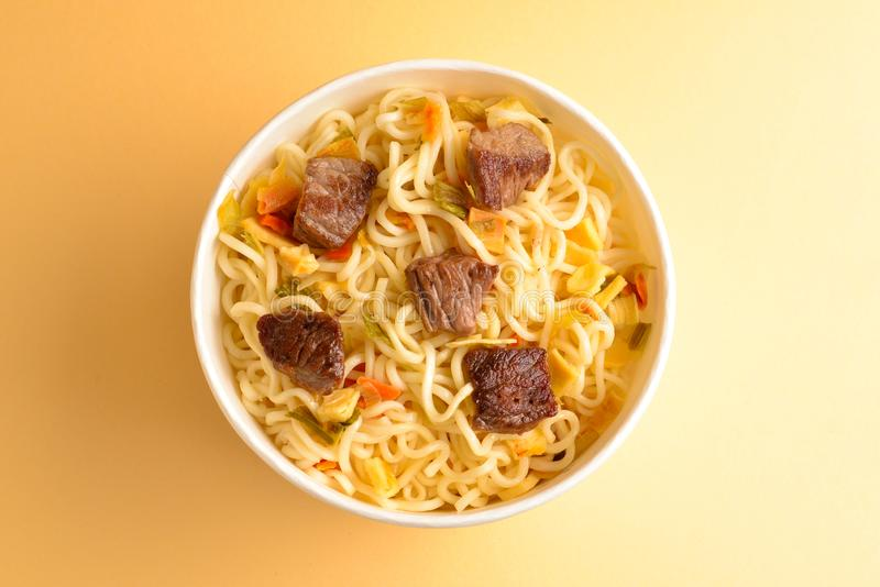 Paper cup with instant ramen noodles with beef and vegetables. Top view stock photo