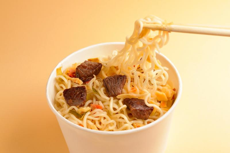 Paper cup with instant ramen noodles with beef and vegetables. Top view stock image