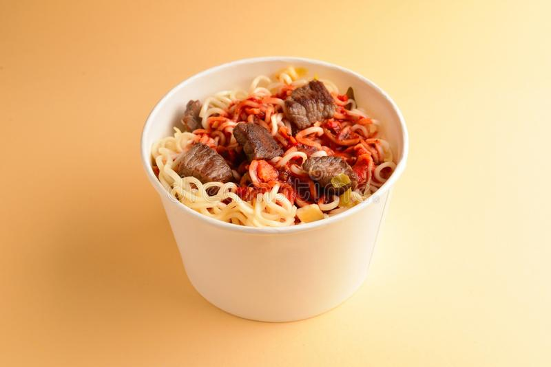 Paper cup with instant ramen noodles with beef and vegetables. Top view royalty free stock photography
