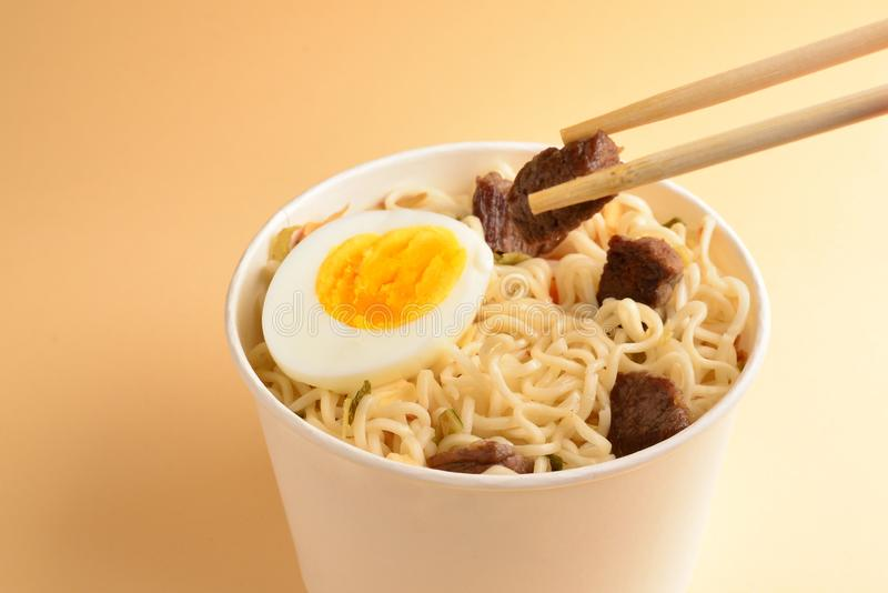 Paper cup with instant ramen noodles with beef and vegetables. Top view. Top view stock photo