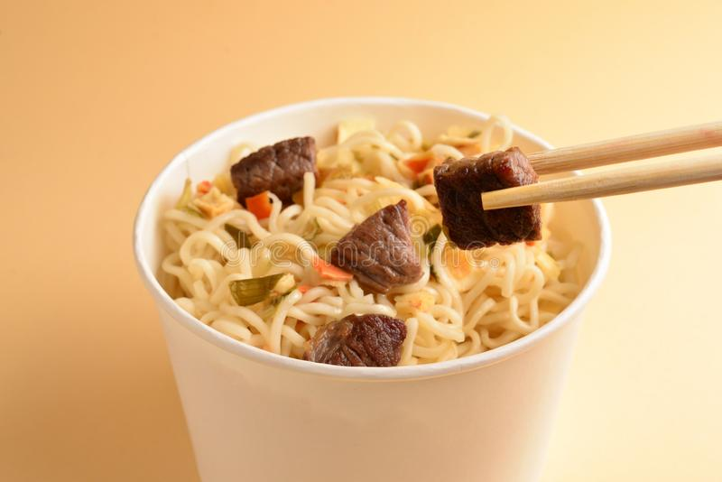 Paper cup with instant ramen noodles with beef and vegetables. Top view royalty free stock photo