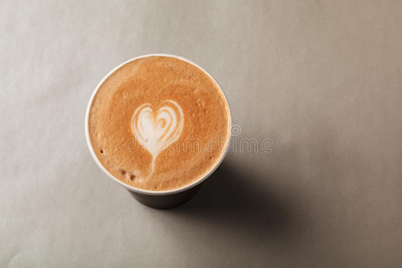 Paper cup of latte or cappuccino with patterned heart latte art on a grey background. Coffee to take away, coffee to go royalty free stock image