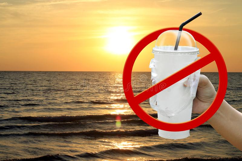 Paper cup white and straws in hand over sea beach sunset evening and stop red sign forbidden symbol, campaign no use and ban stock photo