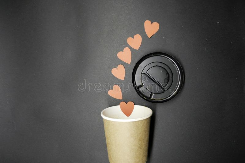 Coffee takeaway cups and red paper hearts. royalty free stock photo