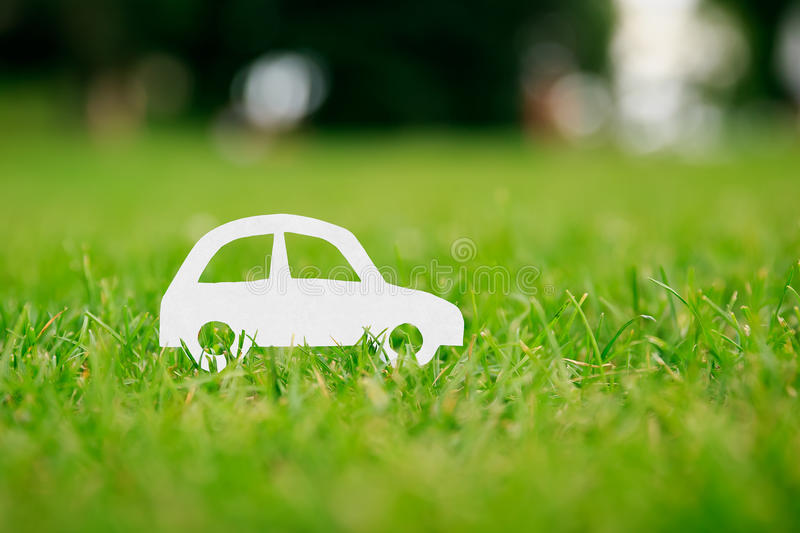 Paper cut of car on green grass. White paper cut of car on green grass royalty free stock photo