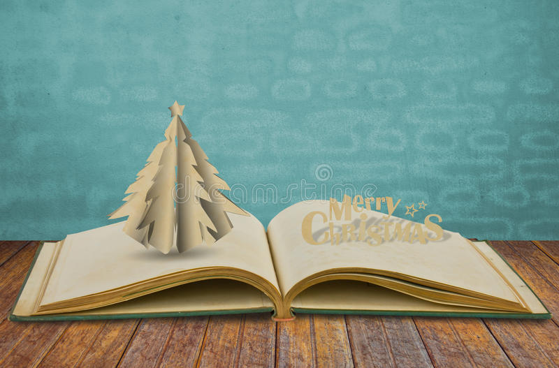 Paper cut of christmas tree on book stock images