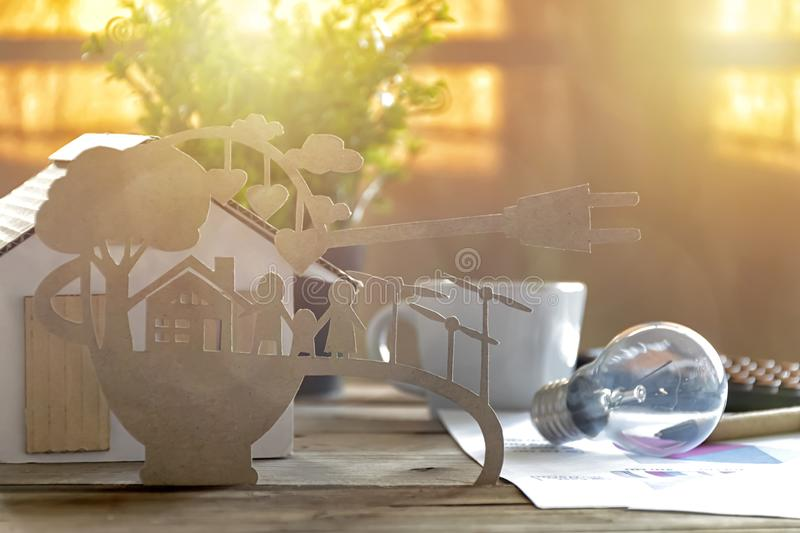 Paper cut of eco on desk. Home model, lamp, pen, document Stories about energy saving, happy families using clean electrical. Energy stock photo