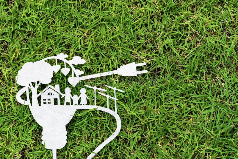 Paper cut of eco on green grass. Stories about energy saving. royalty free stock image