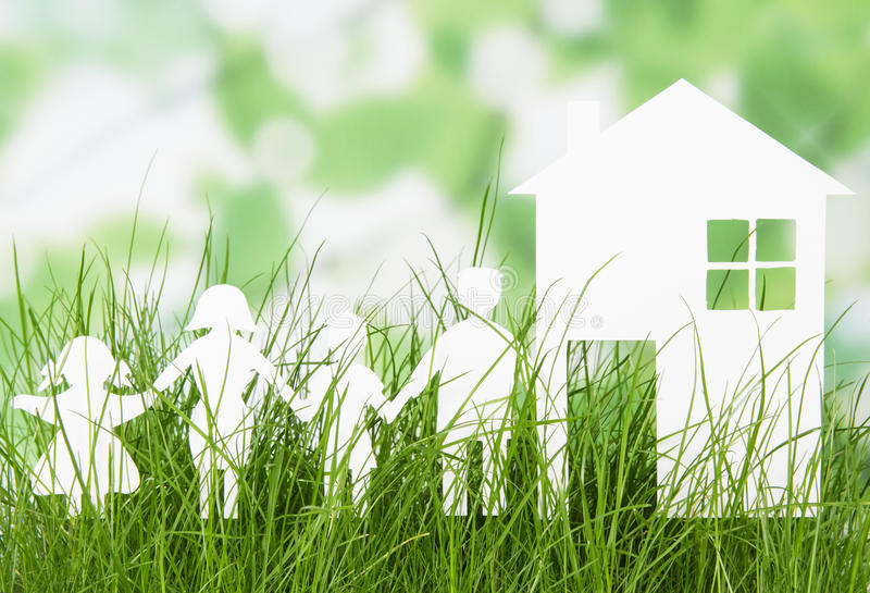 Paper cut of family with house on grass. Paper cut of family with house on fresh spring green grass stock photo
