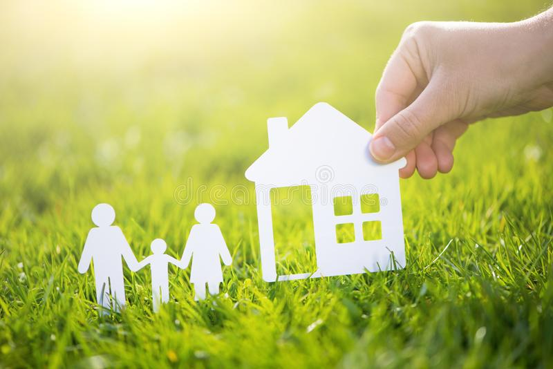 Paper cut family with house in green grass background.  stock photo