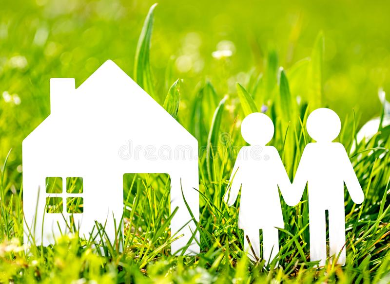 Paper cut family with house in green grass background.  royalty free stock photo