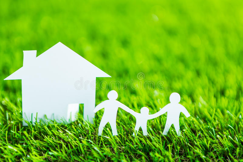Paper cut of family and house on green grass. Paper cut of family with house and tree on fresh spring green grass royalty free stock photography
