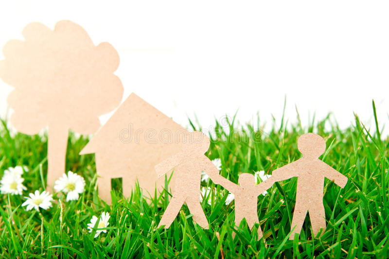 Paper cut of family with house and tree on grass. Paper cut of family with house and tree on fresh spring green grass stock images