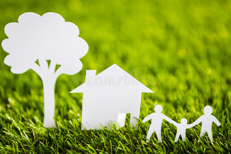 Paper cut of family with house and tree on grass. Paper cut of family with house and tree on fresh spring green grass royalty free stock image