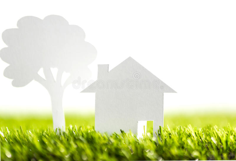 Paper cut of family with house and tree on grass. Paper cut of family with house and tree on fresh spring green grass stock image
