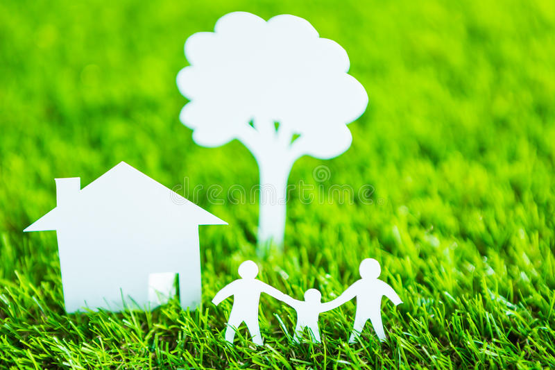 Paper cut of family, house and tree on green grass. Paper cut of family with house and tree on fresh spring green grass stock images