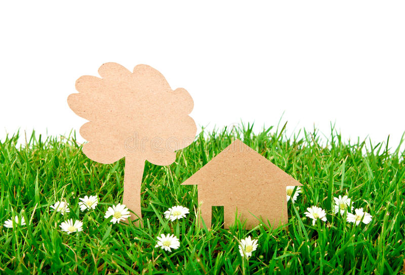 Paper cut of house and tree on grass. Paper cut of house and tree on fresh spring green grass royalty free stock photo