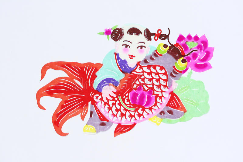 Paper-cut of kid and fish. Paper-cutting is a traditional Chinese folk art. Paper-cut of a kid carrying fish represents good luck and happiness stock photos